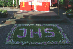 Tapetes de sal, flores, tecido e outros materiais para a passagem de Cristo
